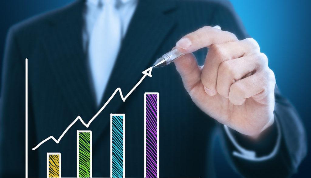 businessman writing rising graph ,blue background